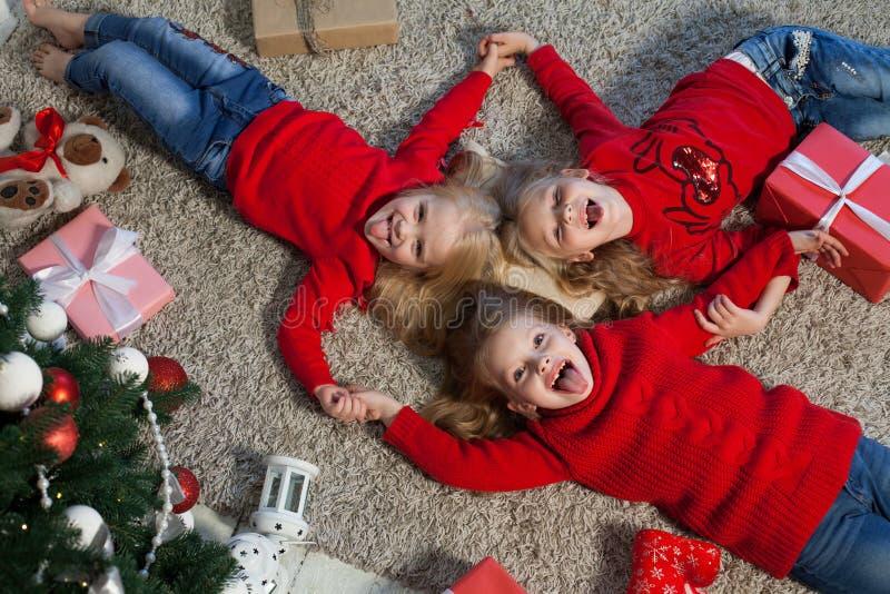 Tres muchachas abren luces de la guirnalda del árbol de navidad del Año Nuevo de los regalos de Navidad fotos de archivo libres de regalías