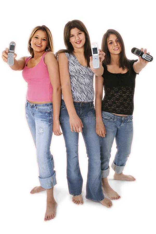 Tres muchachas adolescentes con los teléfonos celulares sobre blanco foto de archivo libre de regalías