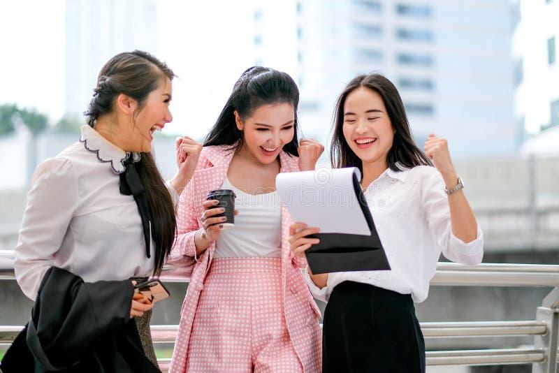 Tres muchachas asiáticas del negocio están actuando tan felices y están excitando fuera de la oficina durante tiempo del día foto de archivo