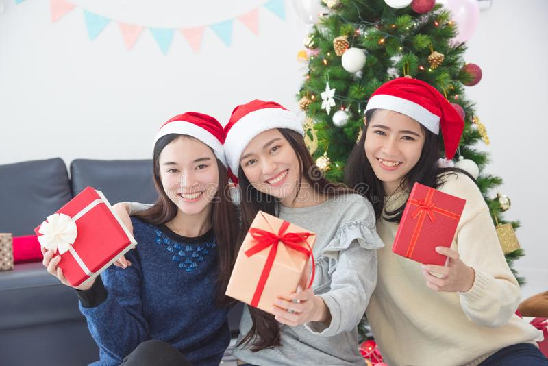 Tres muchachas con la caja y la sonrisa de regalo de la tenencia del sombrero de santa fotos de archivo libres de regalías