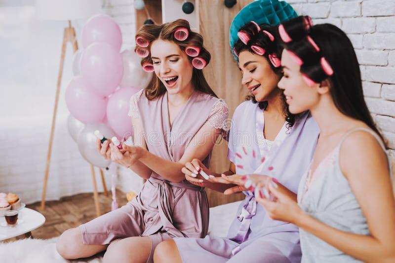 Tres muchachas eligen el esmalte de uñas rosado para la manicura foto de archivo
