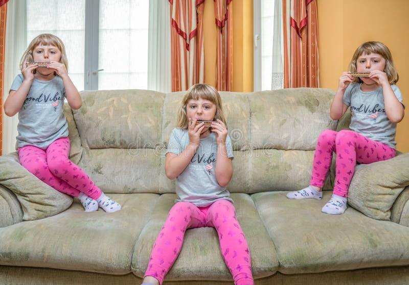 Tres muchachas en el sofá que toca la armónica imagenes de archivo