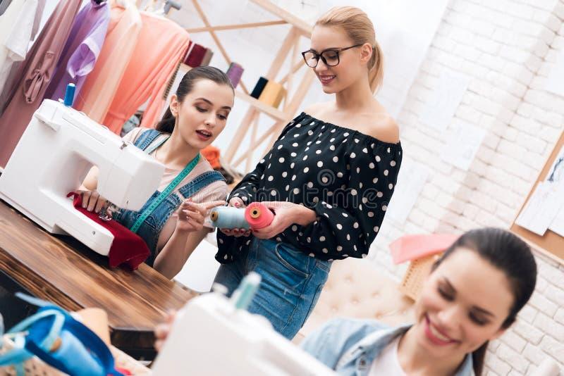 Tres muchachas en la fábrica de la ropa Se están sentando detrás de las máquinas de coser y el elegir rosca para el nuevo vestido fotos de archivo libres de regalías