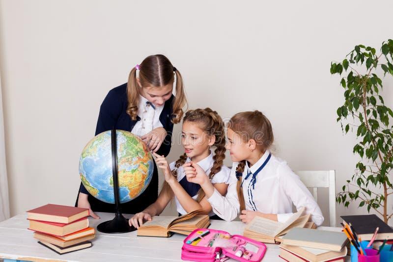 Tres muchachas en la sala de clase que estudian el globo de la geografía de la tierra del planeta imágenes de archivo libres de regalías