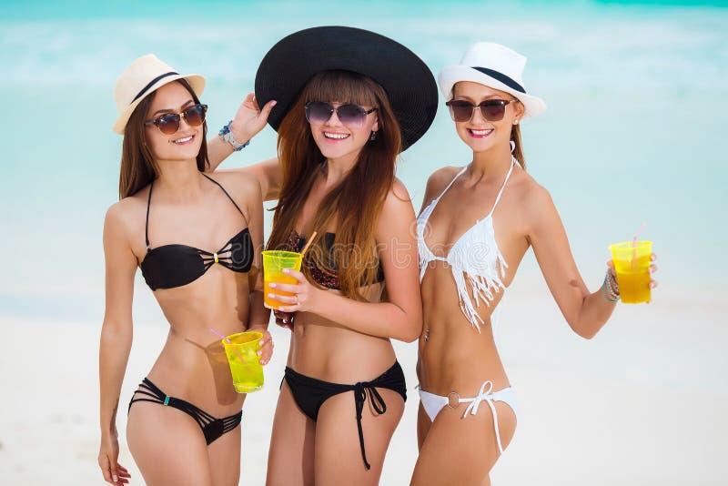 Tres muchachas en sombreros que beben el jugo cerca del mar fotografía de archivo