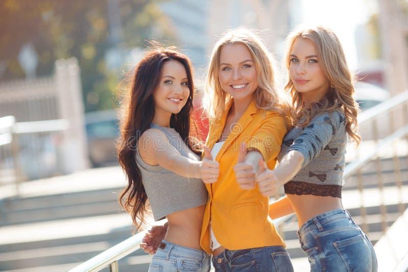 Tres muchachas están caminando en parque del verano imagenes de archivo