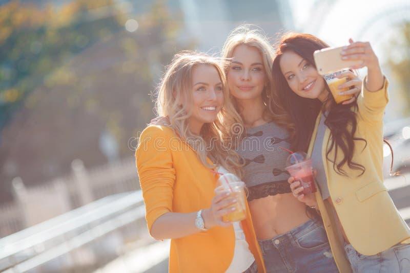 Tres muchachas están haciendo el selfie en el parque fotografía de archivo