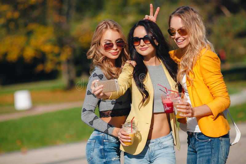 Tres muchachas están haciendo el selfie en el parque imagenes de archivo