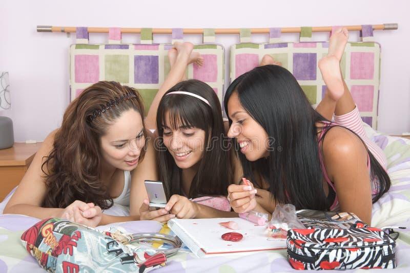 Tres muchachas hermosas que gozan junto en la cama fotos de archivo