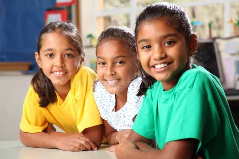 Tres muchachas jovenes de la escuela primaria que se sientan en clase imagenes de archivo