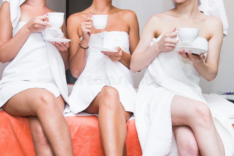 Tres muchachas lindas jovenes en las albornoces blancas están bebiendo té en el salón del balneario Resto después de procedimient fotografía de archivo libre de regalías