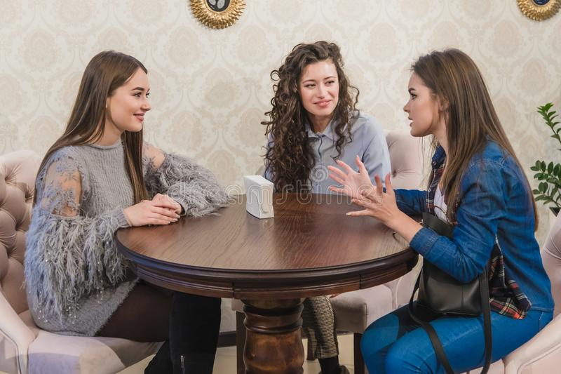 Tres muchachas lindas jovenes se encontraron en un café Durante este tiempo, pidiendo el capuchino, están esperando su orden fotografía de archivo