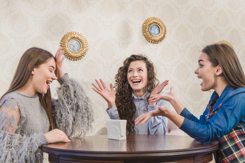 Tres muchachas lindas jovenes se encontraron en un café Durante este tiempo, pidiendo el capuchino, están esperando su orden imagen de archivo libre de regalías
