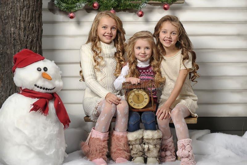 Tres muchachas lindas que esperan la Navidad imágenes de archivo libres de regalías