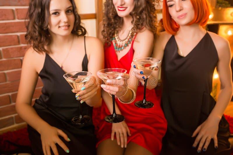 Tres muchachas que celebran su cumpleaños Partido de gallina en vestido idéntico, negro y rojo imagenes de archivo