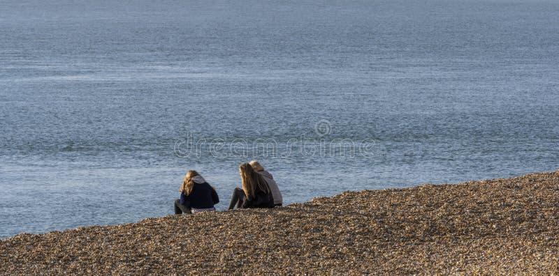 Tres muchachas que se sientan en la playa fotos de archivo
