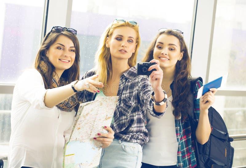 Tres muchachas se colocan en el aeropuerto y la mirada de la tableta Un viaje con los amigos Muchachas que hacen el selfie foto de archivo libre de regalías