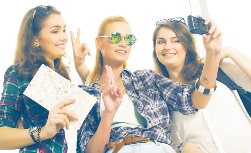 Tres muchachas se colocan en el aeropuerto y la mirada de la tableta Un viaje con los amigos Muchachas que hacen el selfie fotografía de archivo