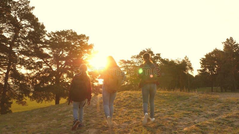 Tres muchachas viajan, caminan a través del bosque para subir la colina para disfrutar y para aumentar sus manos al top Muchacha  imagenes de archivo