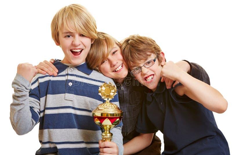 Tres muchachos con animar del trofeo imagen de archivo