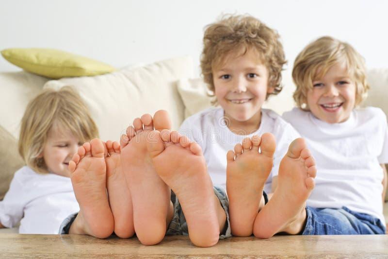 Tres muchachos con los pies desnudos en la tabla imagenes de archivo