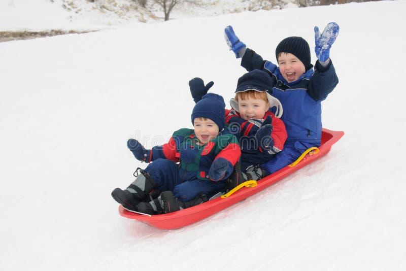 Tres muchachos jovenes sledding cuesta abajo junto fotografía de archivo