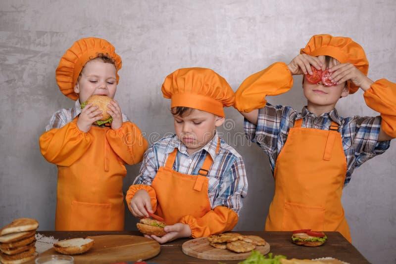 Tres muchachos lindos en los cocineros de los trajes contratados a cocinar las hamburguesas hechas en casa fotos de archivo libres de regalías