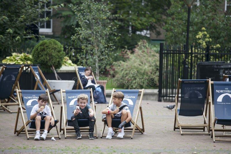 Tres muchachos seis años están comiendo el helado que se sienta en deckchairs en el parque fotos de archivo libres de regalías