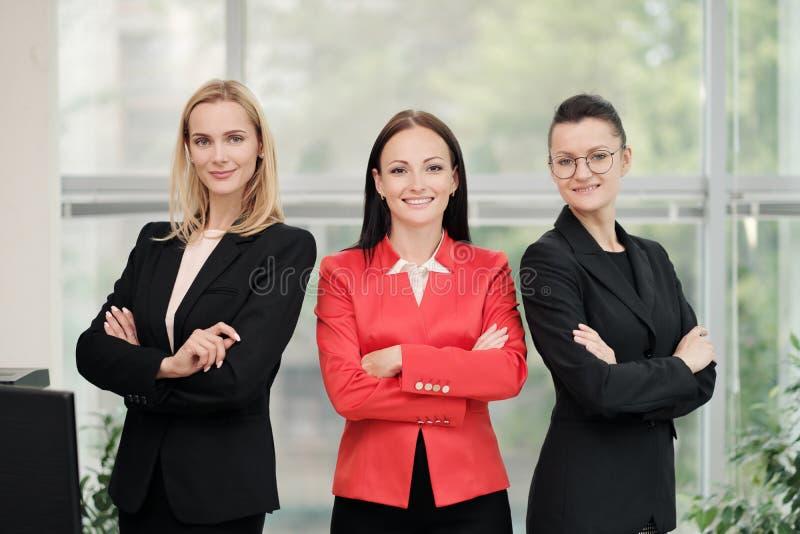 Tres mujeres atractivas jovenes en los trajes de negocios que presentan contra el contexto de una oficina ligera Cabeza y subordi imagen de archivo