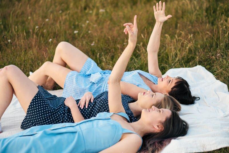 Tres mujeres atractivas jovenes están mintiendo en una tela escocesa y están mirando el cielo Risa y destacar, danza Novias del r foto de archivo libre de regalías