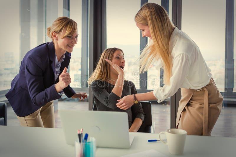 Tres mujeres de negocios en oficina moderna que celebran buen proyecto resultan imagen de archivo