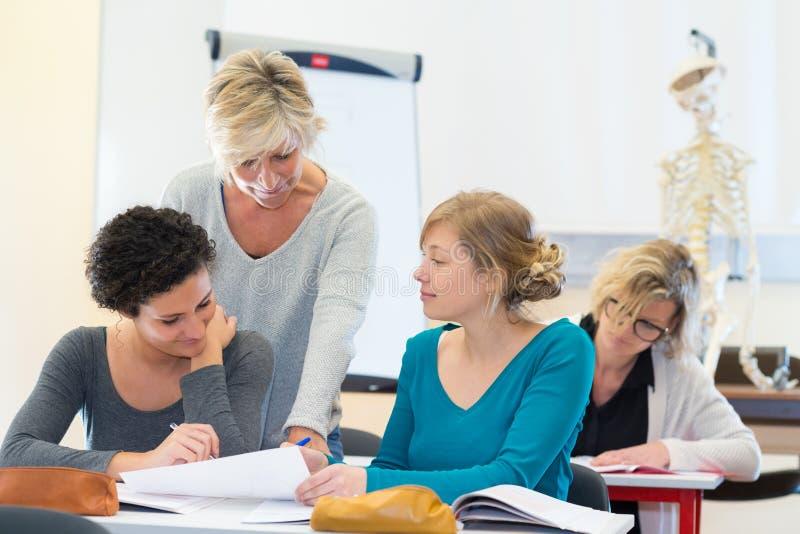 Tres mujeres en sala de clase con el profesor fotografía de archivo libre de regalías