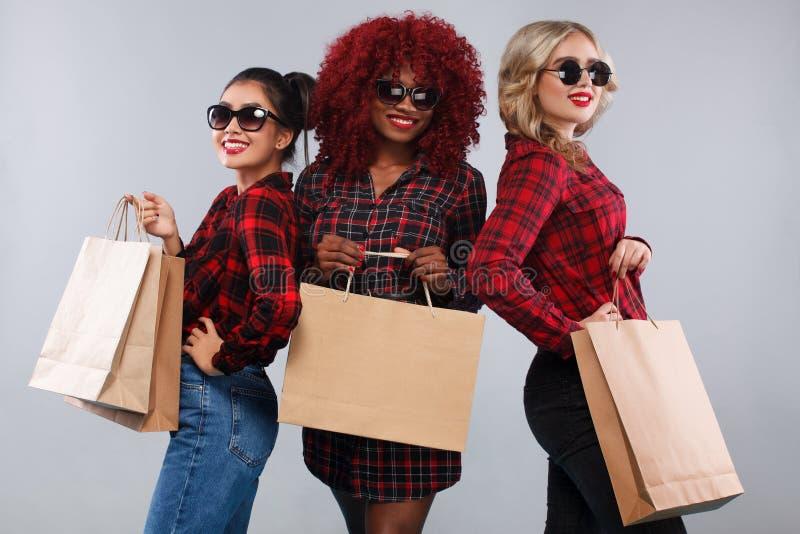 Tres mujeres felices en gafas de sol Razas afroamericanas, asiáticas y caucásicas El hacer compras con aislado en fondo gris ence fotografía de archivo