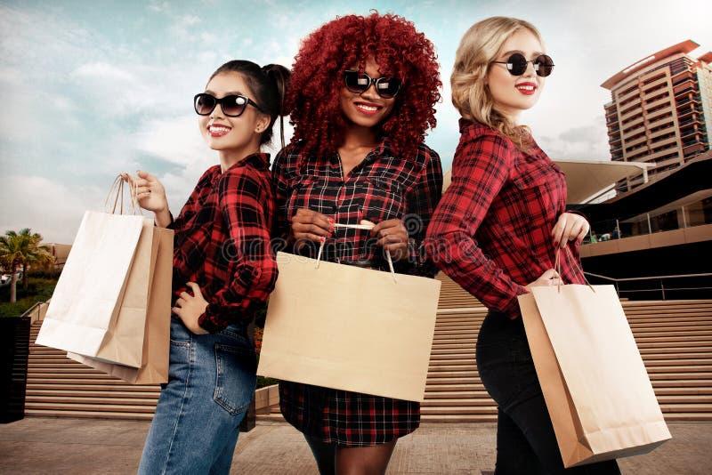 Tres mujeres felices en gafas de sol Razas afroamericanas, asiáticas y caucásicas El hacer compras en el día de fiesta negro de v foto de archivo