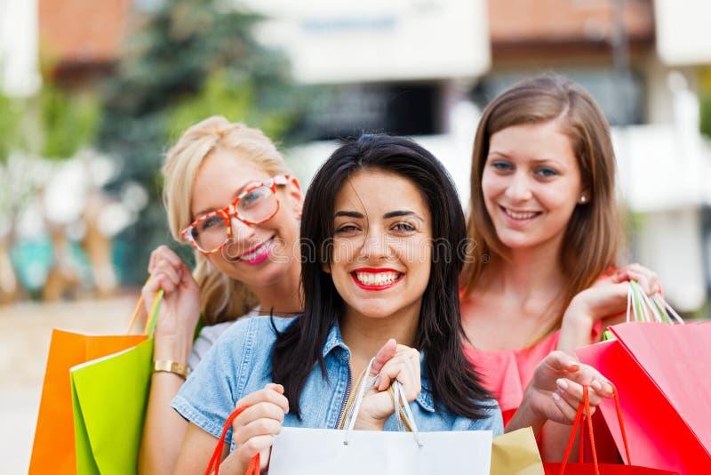 Tres mujeres hacia fuera en compras de la ciudad fotos de archivo