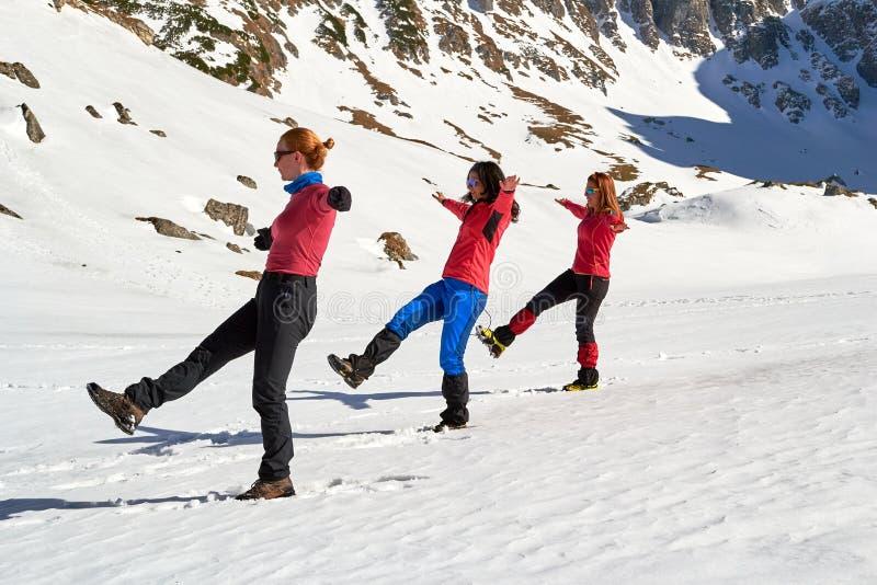 Tres mujeres haciendo un balance sincrónico posan en la nieve, en un soleado día de invierno en las montañas de Bucegi, Rumania foto de archivo