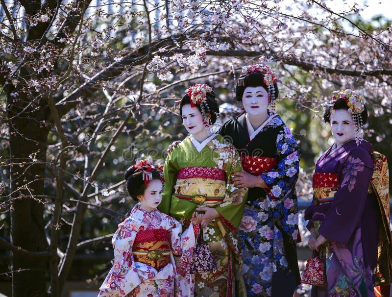 Tres mujeres hermosas y una niña maravillosa en el kimono de Maiko se visten foto de archivo