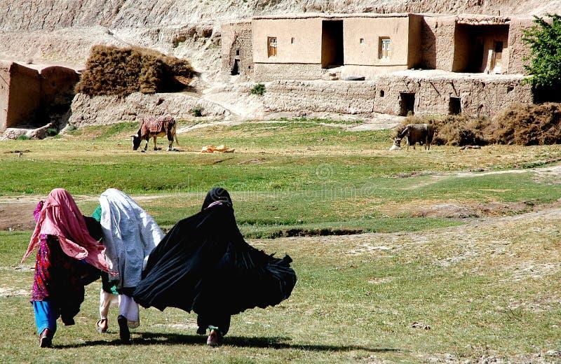 Tres mujeres jóvenes cruzan un campo en una pequeña aldea entre Chaghcharan y el Minaret of Jam en Afganistán fotos de archivo