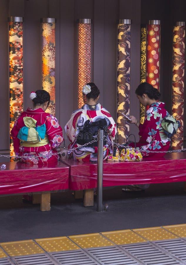Tres mujeres japonesas que se sientan en kimonos fotografía de archivo