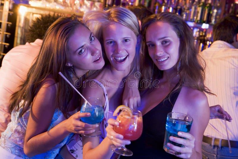 Tres mujeres jovenes con las bebidas en un club nocturno fotografía de archivo