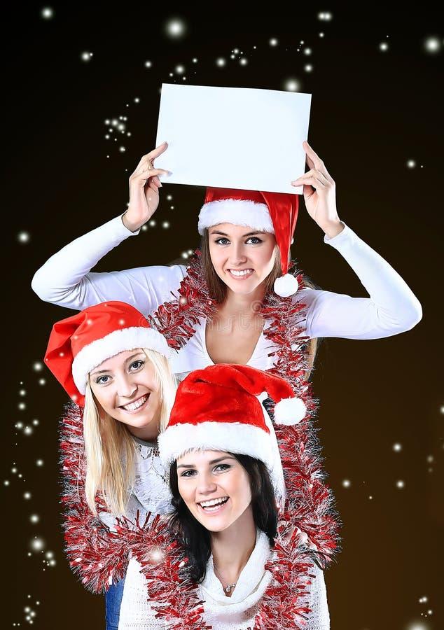 Tres mujeres jovenes en el traje de Santa Claus con compras en el fondo de la Navidad fotografía de archivo