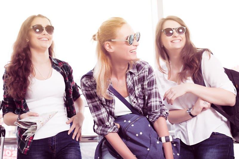 Tres mujeres jovenes en las gafas de sol que se colocan en el aeropuerto y el laug fotos de archivo libres de regalías
