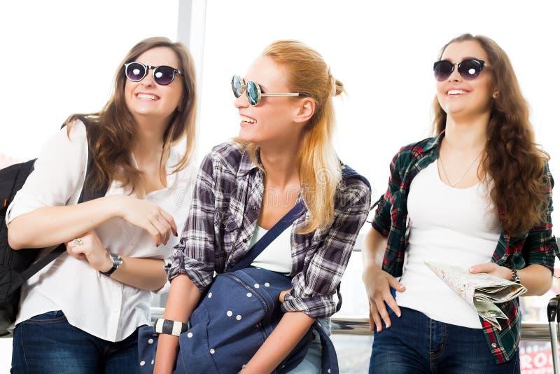 Tres mujeres jovenes en las gafas de sol que se colocan en el aeropuerto y la risa Un viaje con los amigos imagen de archivo libre de regalías
