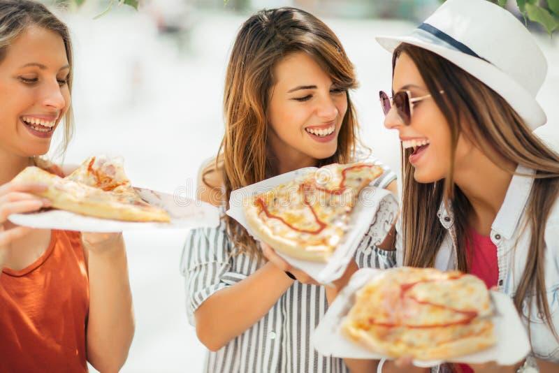 Tres mujeres jovenes hermosas que comen la pizza después de hacer compras imagen de archivo libre de regalías