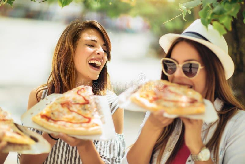 Tres mujeres jovenes hermosas que comen la pizza después de hacer compras imágenes de archivo libres de regalías
