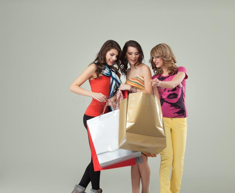 Tres mujeres jovenes hermosas que sostienen bolsos de compras imagenes de archivo