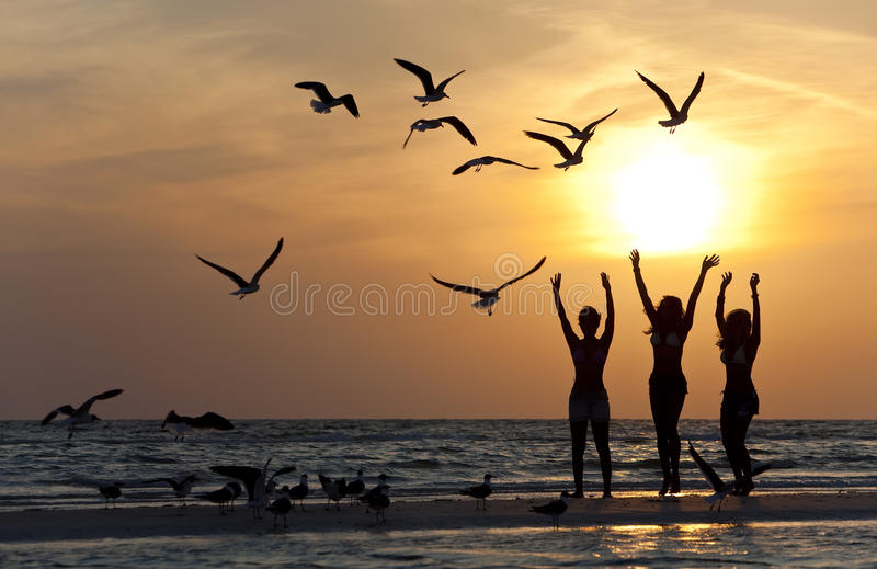 Tres mujeres jovenes que bailan en la playa en la puesta del sol foto de archivo