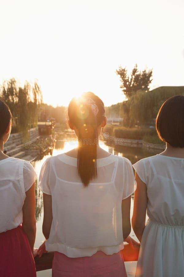 Tres mujeres jovenes que consideran rio abajo una puesta del sol fotos de archivo