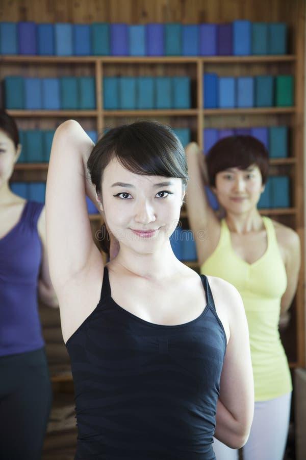 Tres mujeres jovenes que estiran y que hacen la yoga, mirando la cámara, foto de archivo libre de regalías