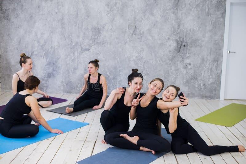 Tres mujeres jovenes que hacen el selfie después de entrenamiento en la clase de la yoga fotografía de archivo